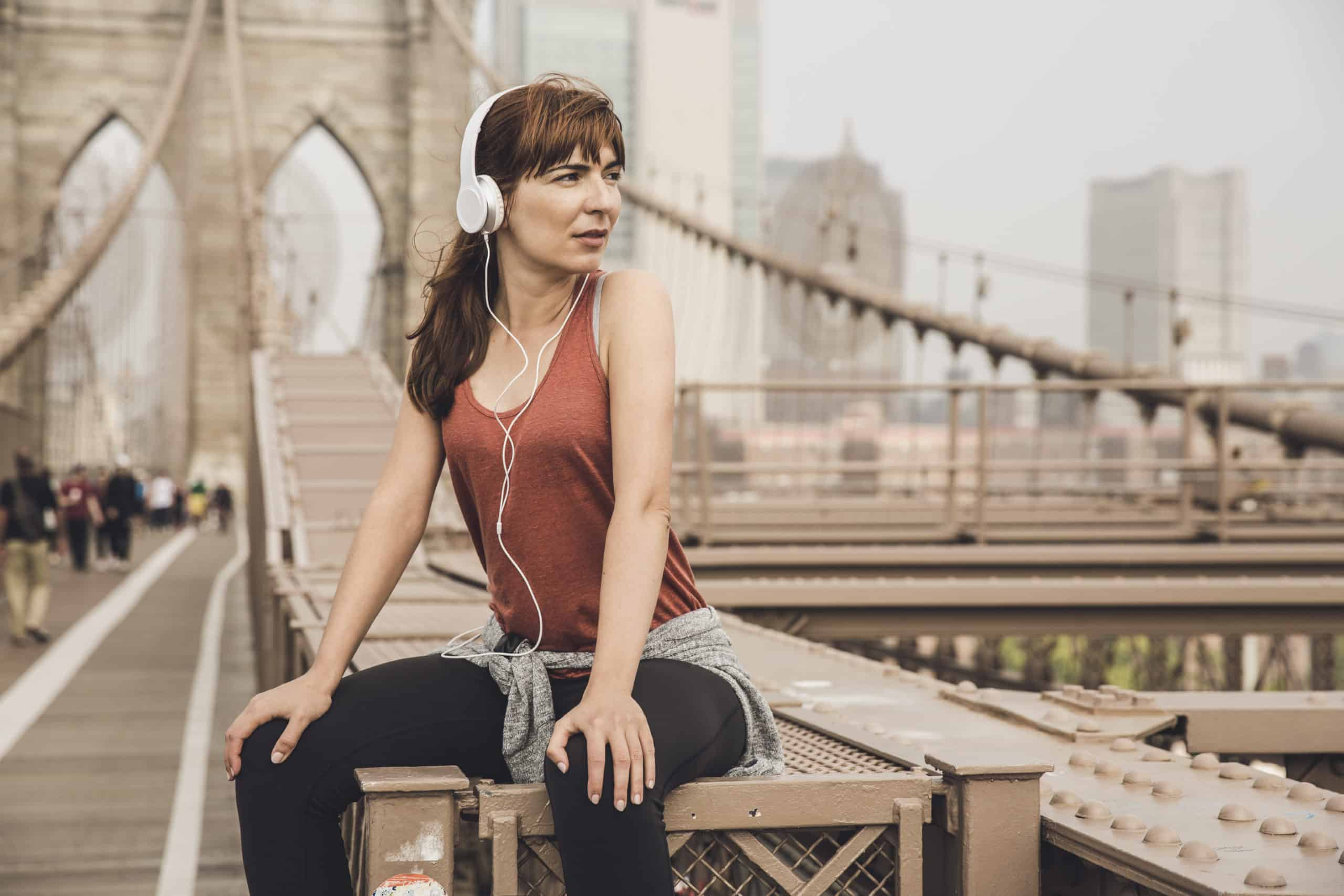 Woman sitting on the Brooklyn bridge and looking  the view