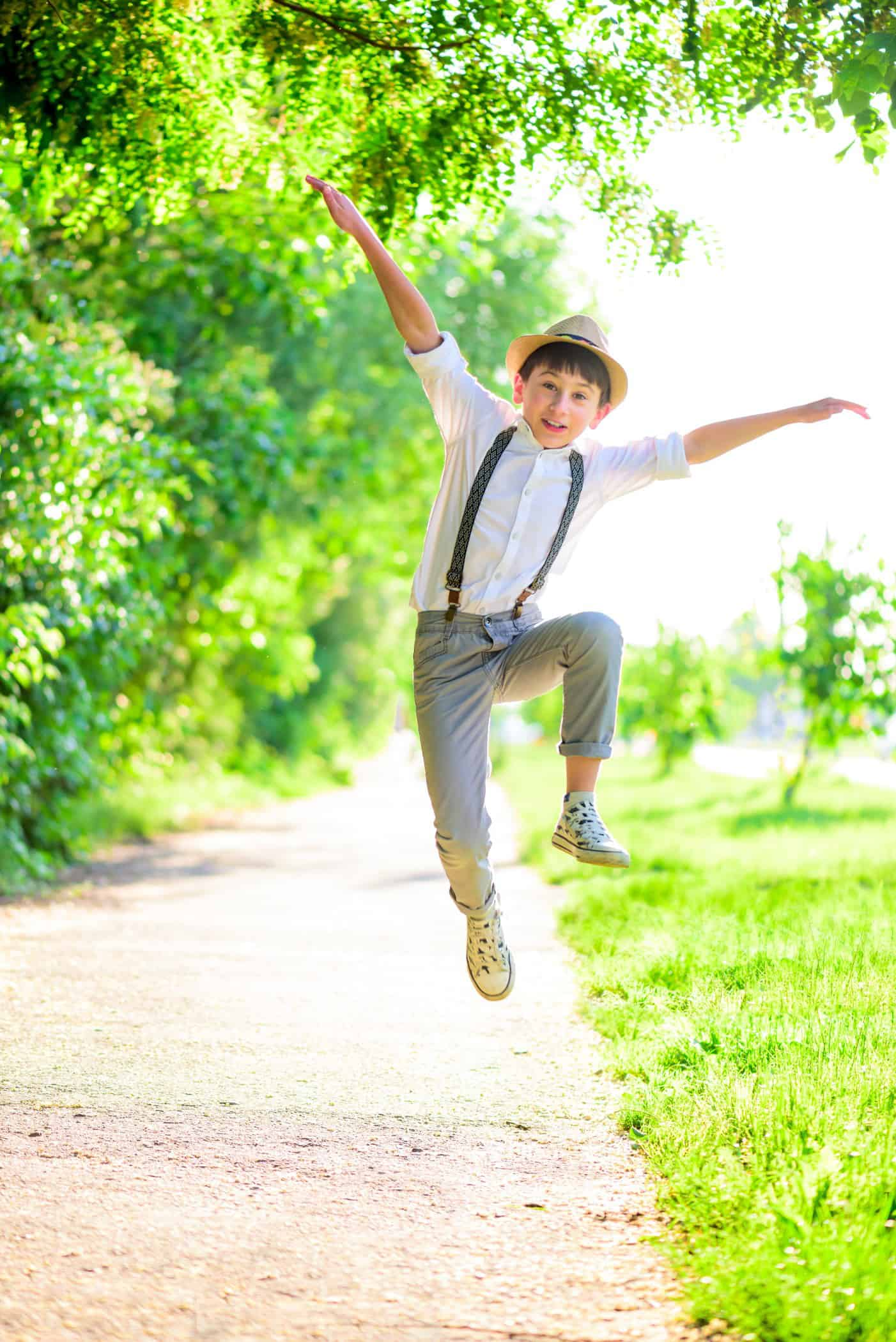 happy-boy-jumping-on-street-against-green-grass-soft-focus-summer-activities_t20_BajgPO 2
