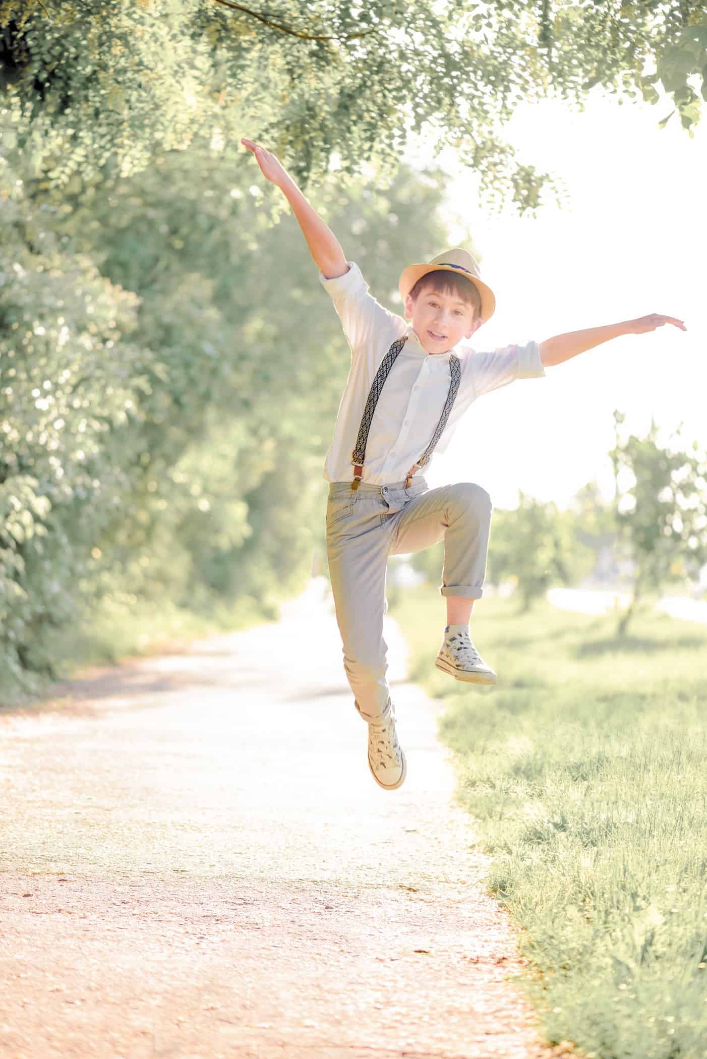 happy-boy-jumping-on-street-against-green-grass-soft-focus-summer-activities_t20_BajgPO