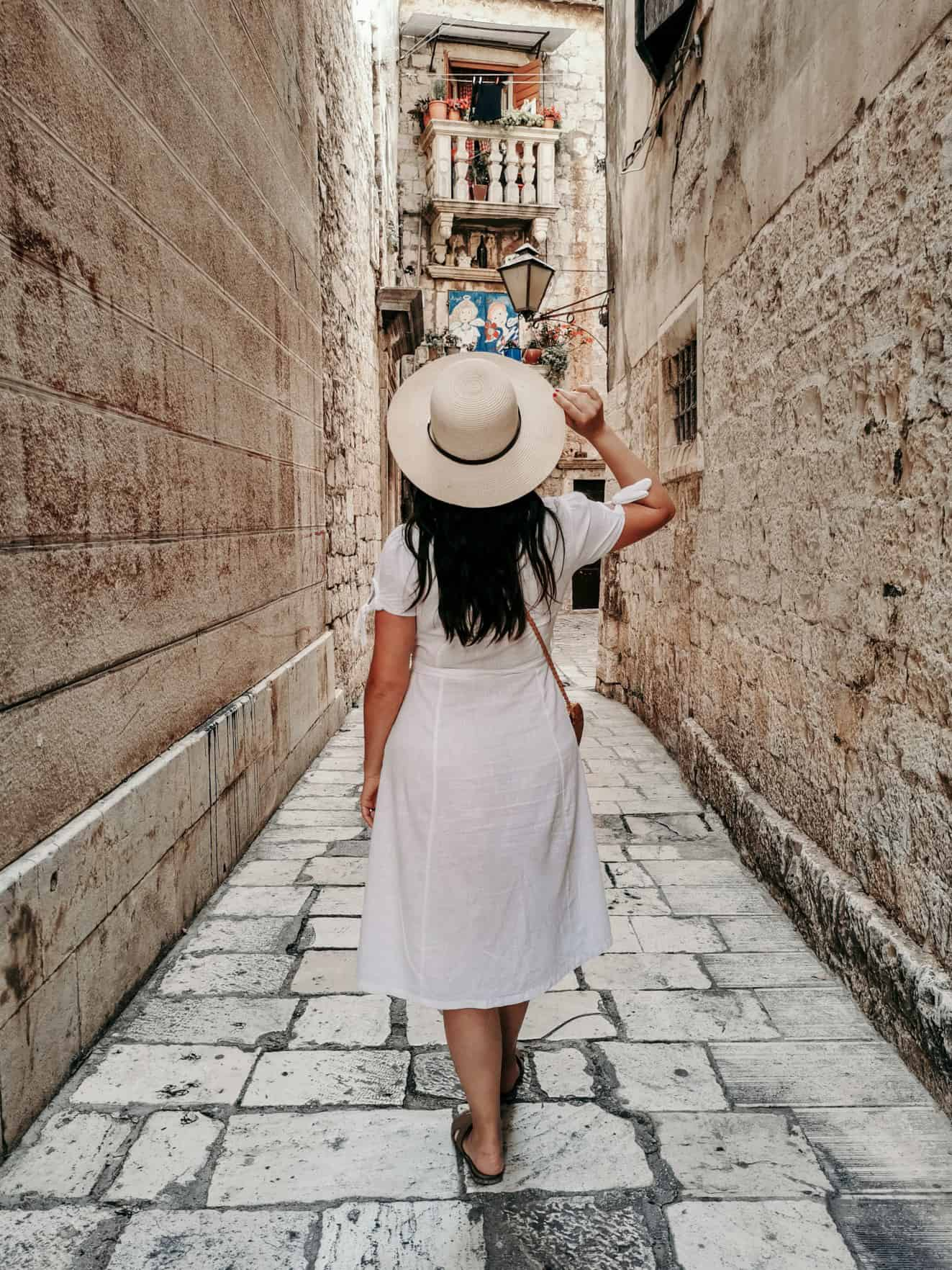 rear-view-of-stylish-young-woman-wearing-sun-hat-and-white-summer-style-dress-walking-on-stone-paved_t20_NlV9XN 2