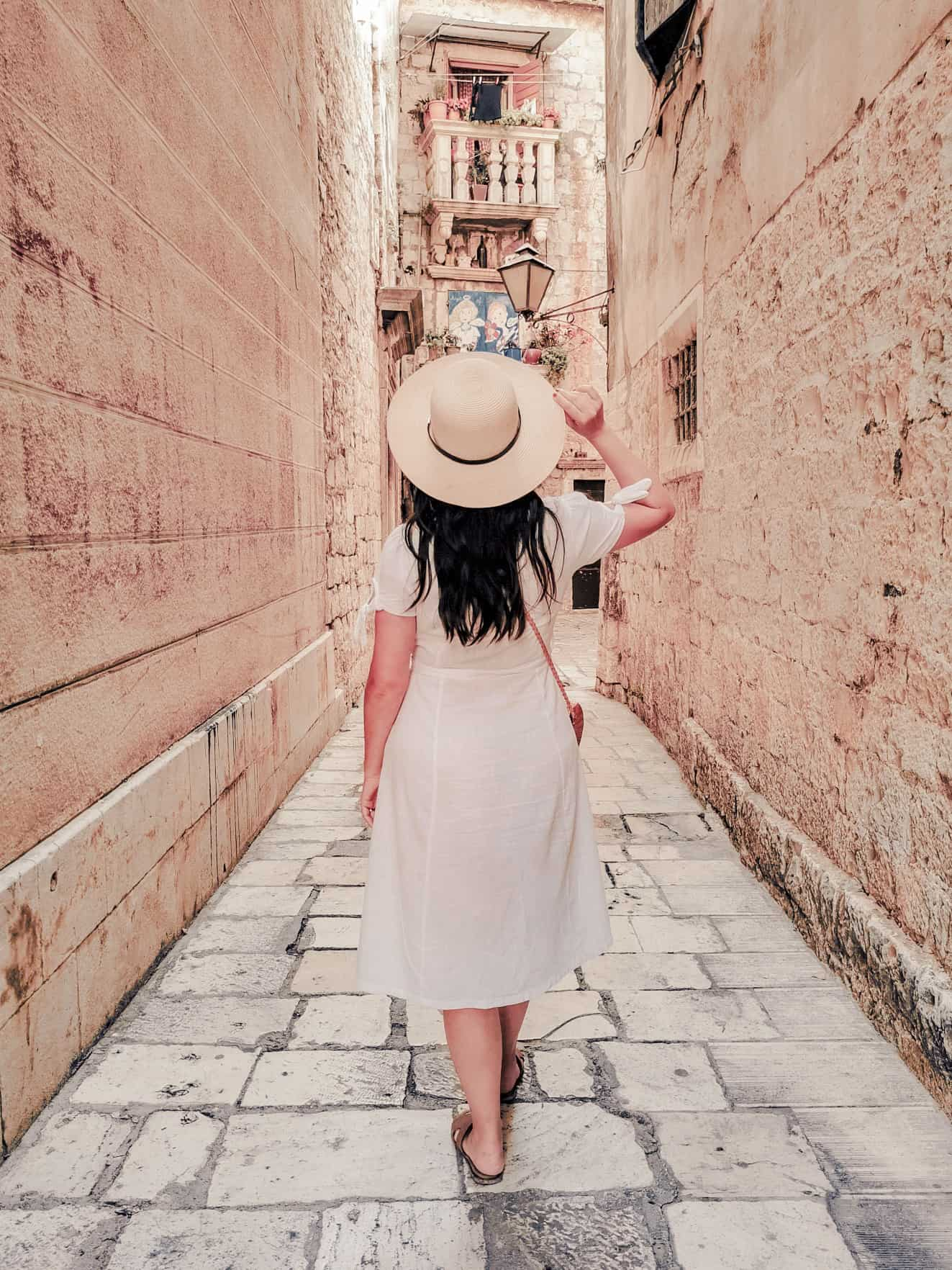 rear-view-of-stylish-young-woman-wearing-sun-hat-and-white-summer-style-dress-walking-on-stone-paved_t20_NlV9XN
