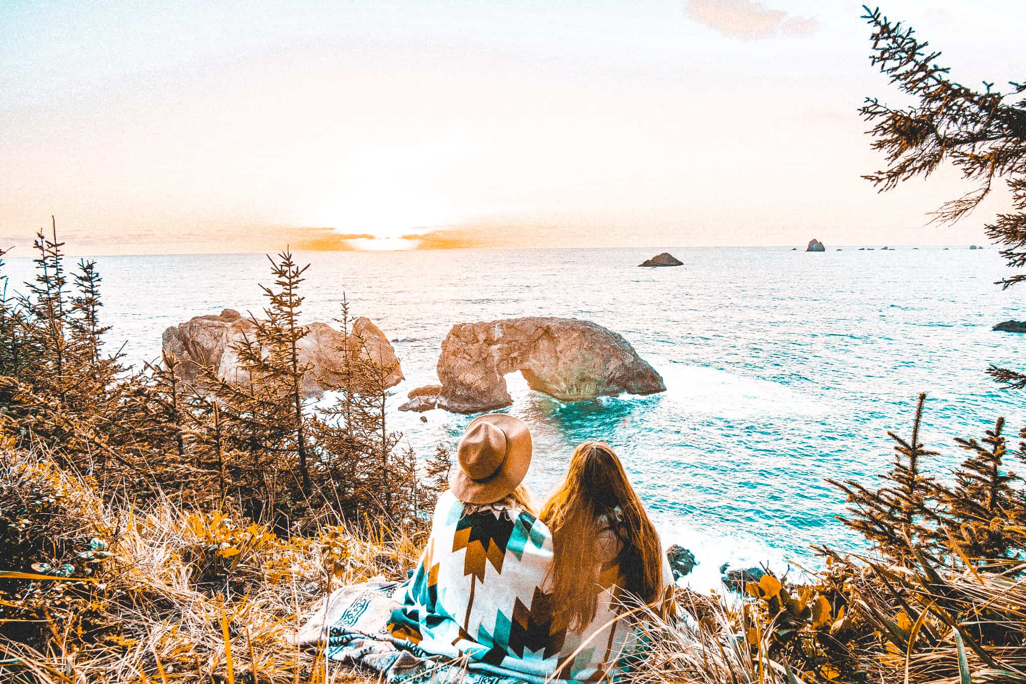 two-women-sitting-on-a-cliff-overlooking-the-ocean-watching-the-sunset_t20_WxxNW4 2