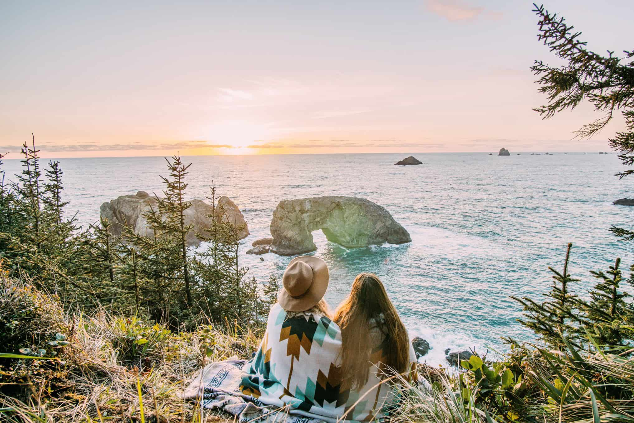 two-women-sitting-on-a-cliff-overlooking-the-ocean-watching-the-sunset_t20_WxxNW4